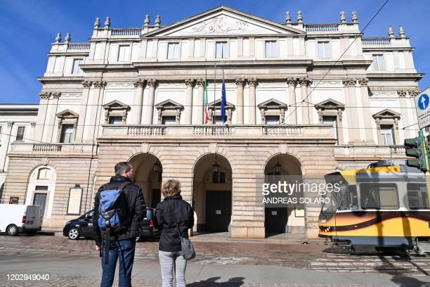Two people look at the La Scala theatre in central Milan on February 24 2020 closed following security measures taken in northern Italy against the...
