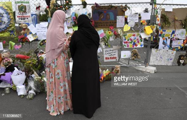 Two people look at tributes left at the Linwood Islamic Centre which remains closed despite the reopening of city's Al Noor mosque, in Christchurch...