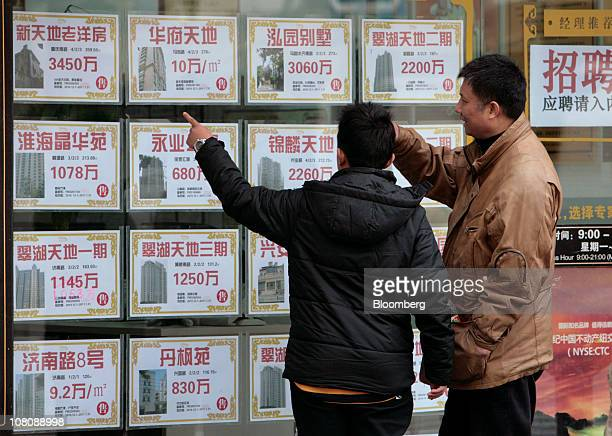 Two people look in a real estate agents window in Shanghai China on Monday Jan 17 2011 Shanghai China's financial center will this year prepare for a...