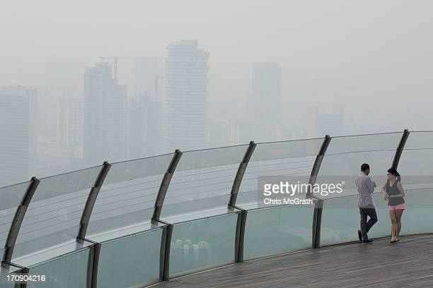 Two people look out over the smoke shrouded Singapore skyline from the Marina Bay Skypark on June 20, 2013 in Singapore. The Pollutant Standards...