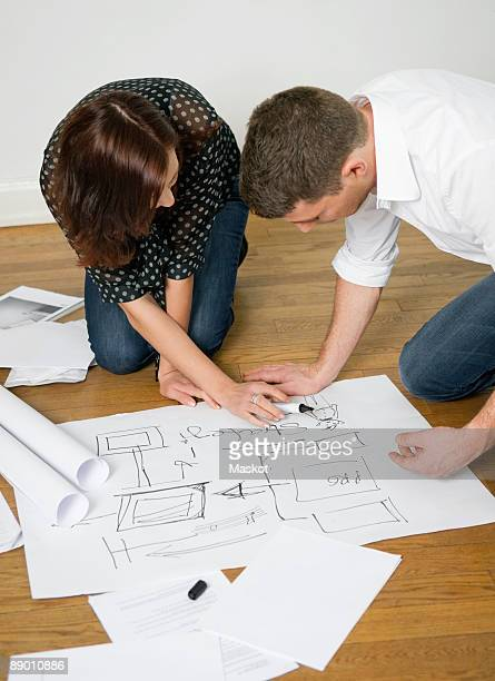 Two people looking at blueprints on floor