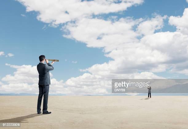 deux personnes qui cherchent à l'autre par le biais de spyglasses - longue vue photos et images de collection