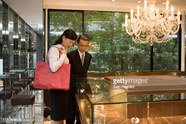 two people looking at jewelry in display cabinets - stereotypically upper class stock pictures, royalty-free photos & images