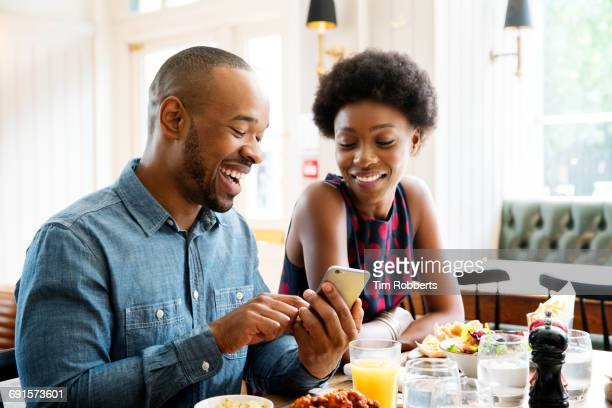 Two people looking at phone with lunch.
