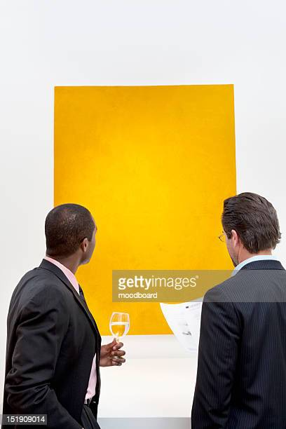 Two people looking at yellow painting on wall in art gallery