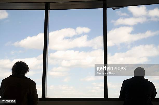 two people looking out large windows - erker stockfoto's en -beelden