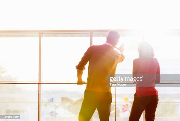 two people looking out window - gegenlicht stock-fotos und bilder