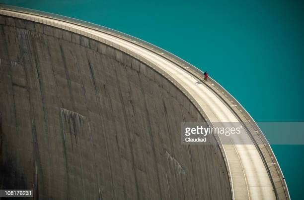 Two People Looking Over the Edge of a Large Dam