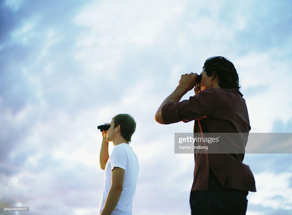 Two people looking through binoculars, low angle view : Stockfoto