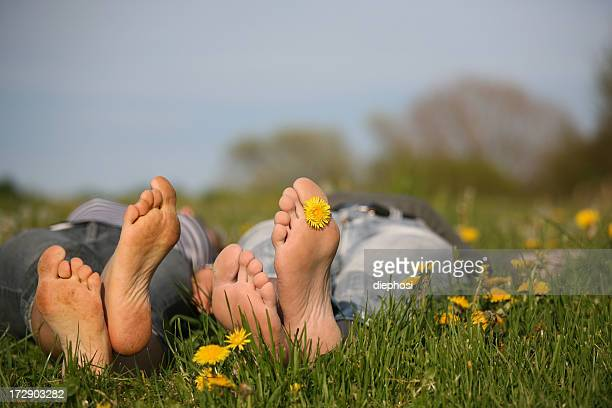 Two people lying barefoot in grass with yellow flowers