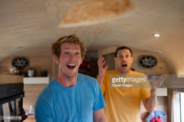 two people making funny face while flipping crepes inside school bus - pancakes stock pictures, royalty-free photos & images