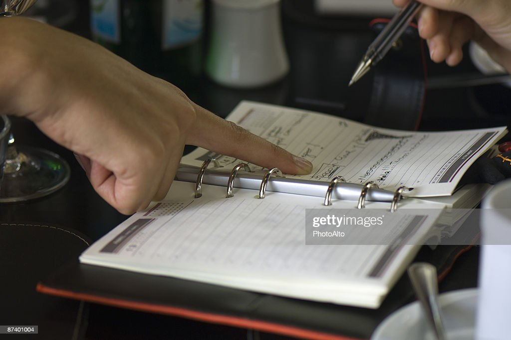 Two People Making Plans Using Agenda One Holding Pen While