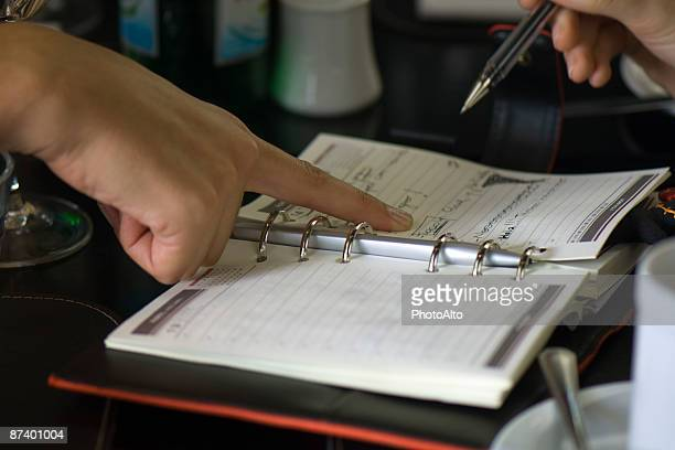 two people making plans using agenda, one holding pen while the other points to page - time management stock photos and pictures