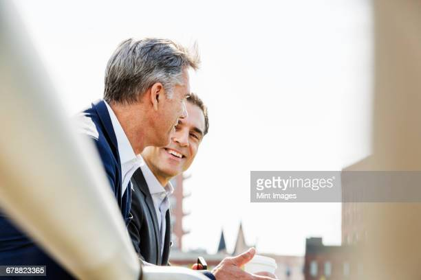 Two people, men talking together outdoors leaning on a railing, taking a coffee break.