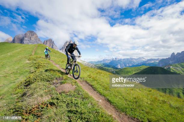 two people mountain biking above passo sella, val gardena, south tyrol, italy - extreme sports stock pictures, royalty-free photos & images