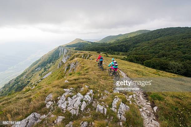 Two people mountain biking on a trail near Vipava, Slovenia