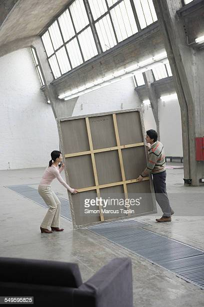 two people moving a painting - kunsthändler stock-fotos und bilder