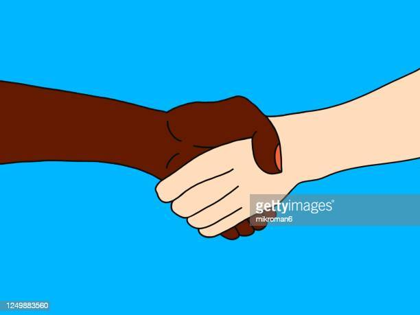 two people of different races, white and black, shaking hands - anti racism stock pictures, royalty-free photos & images