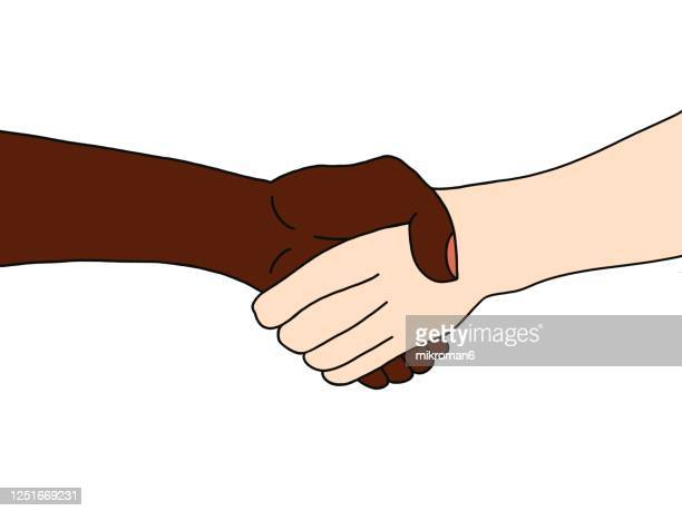 two people of different races, white and black, shaking hands - social movement stock pictures, royalty-free photos & images