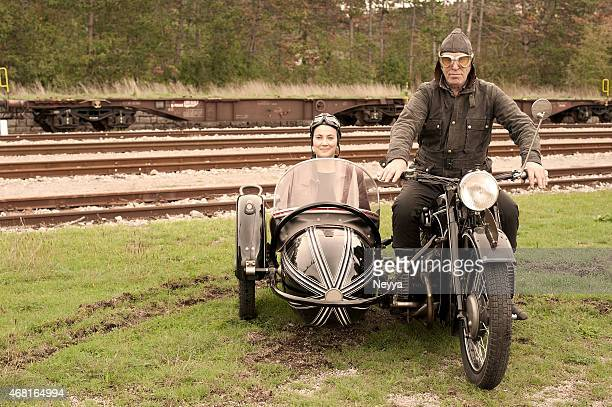 Two people on a 1935 style motorcycle with sidecar
