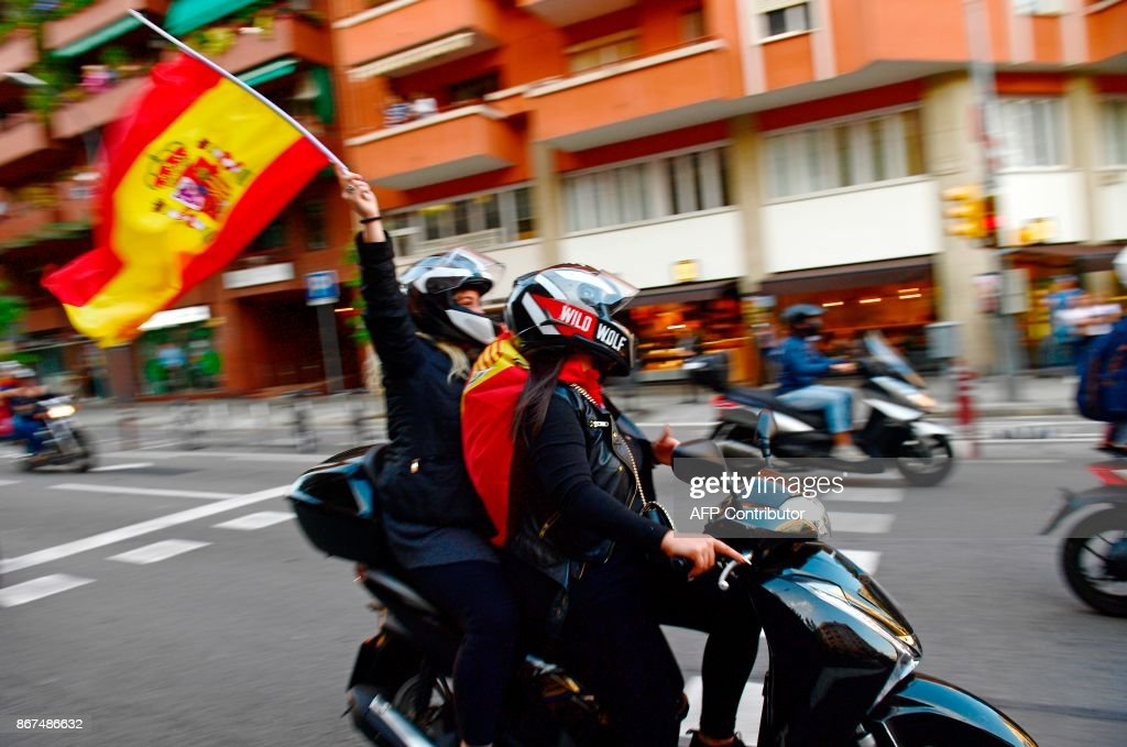 Two people on a bike hold Spanish flags during a demonstration calling for unity in Barcelona on October 28, 2017, a day after direct control was imposed on Catalonia over a bid to break away from Spain. Spain moved to assert direct rule over Catalonia, replacing its executive and top functionaries to quash an independence drive that has plunged the country into crisis and unnerved secession-wary Europe. /