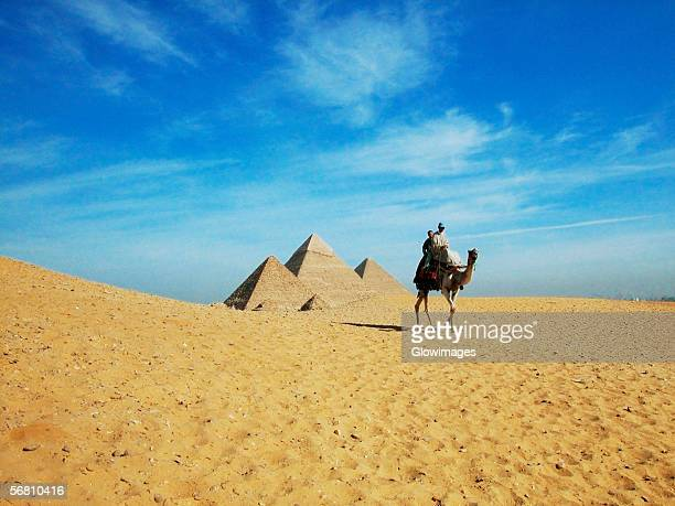 Two people on a camel in front of the pyramids, Giza Pyramids, Giza, Cairo, Egypt