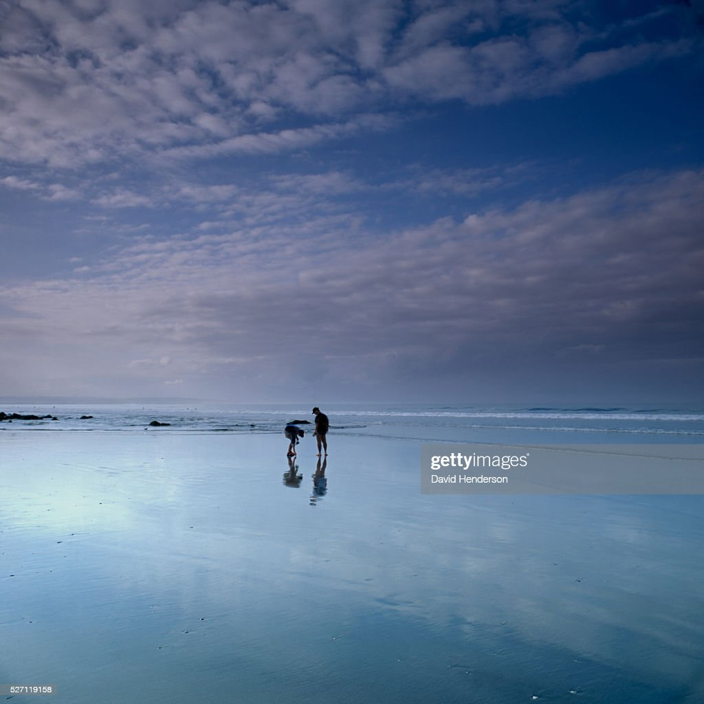 Two people on beach at dusk : Stockfoto