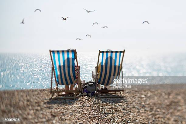 Two people on deckchairs and seagulls