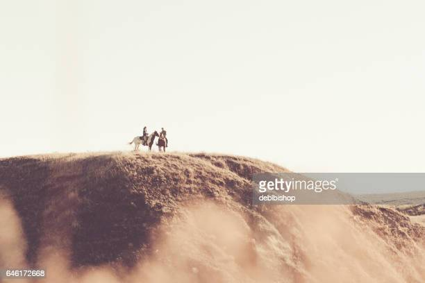 Two People On Hoseback On Top Of Hill