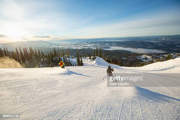 Two people on ski slope at sunlight