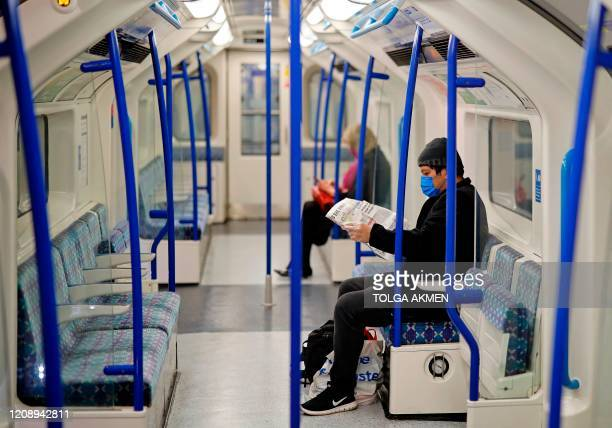Two people, one wearing a face mask as a precautionary measure against COVID-19, sit on an empty TfL underground tube carriage as they travel on the...
