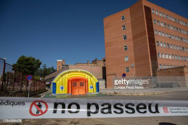 Two people pass by a campaign hospital prepared to care for coronavirus patients next to the Arnau University Hospital at Lleida, capital of the...