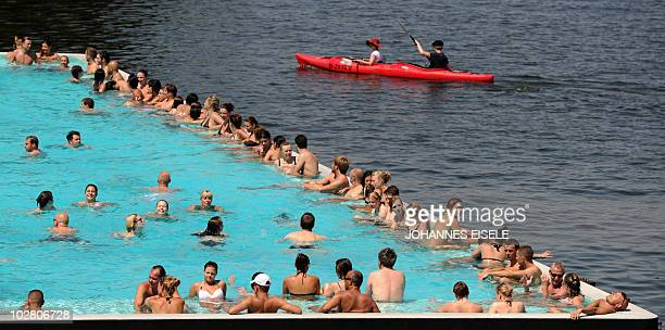 Two people pass the socalled 'Badeschiff' in a canoe in the river Spree on July 11 2010 in Berlin as the country experiences a heatwave with...