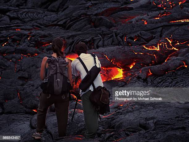 Two people photographing lava streams in Hawaii