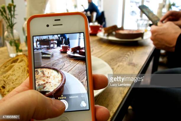 Two people photographing their food in a café with their smartphones