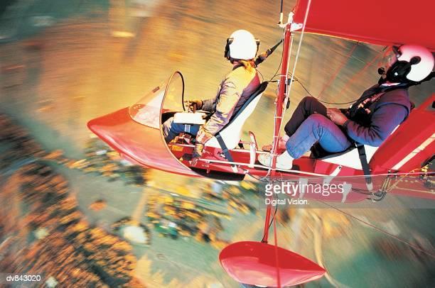 two people piloting a small aircraft - aereo ultraleggero foto e immagini stock
