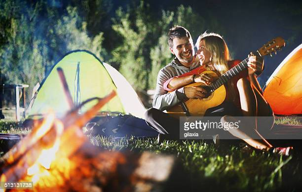 Two people playing guitar by campfire.