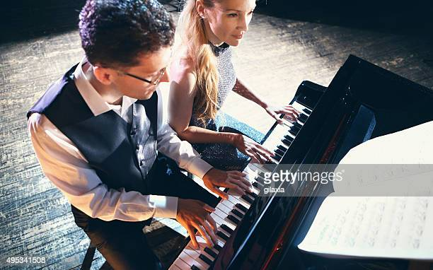 Two people playing piano.
