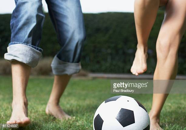 Two people playing soccer outdoors