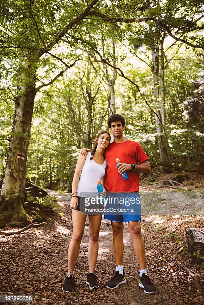 two people pose on a trail - middlebare afstand stockfoto's en -beelden