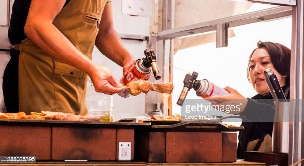 Two people preparing food at Tsukiji Fish market in Tokyo in Japan.