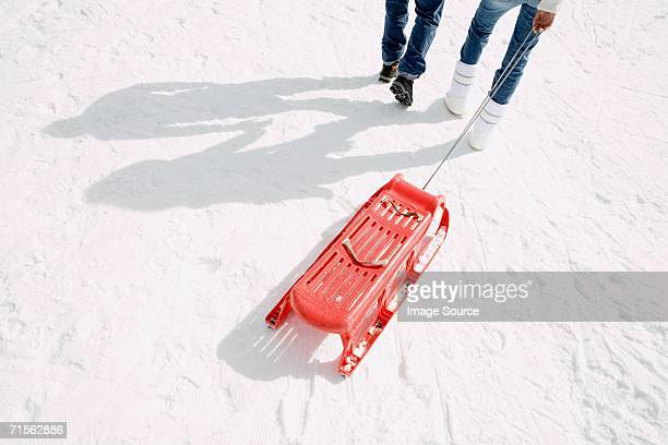 Two people pulling a sleigh