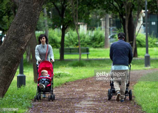 Two people push strollers in a park in Seville on April 26, 2020 amid a national lockdown to prevent the spread of the COVID-19 disease. - After six...