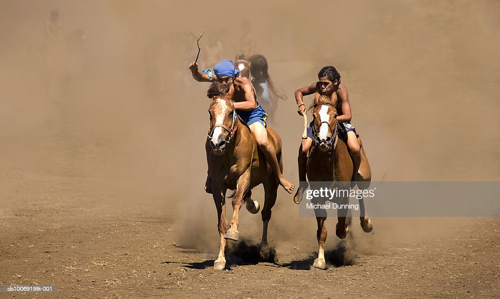 Two people racing on horses : Stockfoto