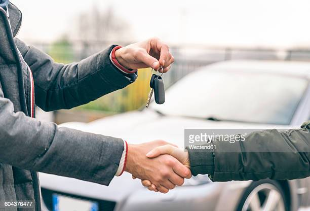 Two people reaching an agreement about a car sale