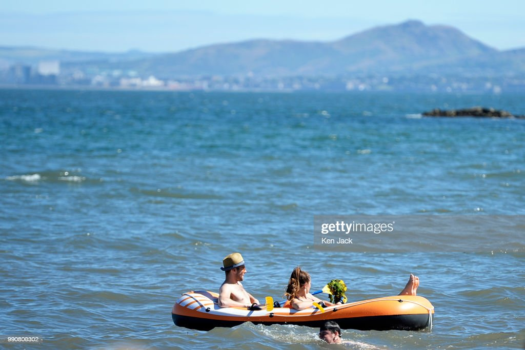 Two people relax in an inflatable dinghy off Silver Sands beach at the start of the Scottish school holidays as the heatwave continues, with Edinburgh in the background across the Firth of Forth, on July 3, 2018 in Aberdour, Scotland.