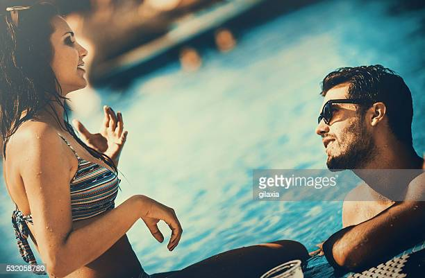 Two people relaxing by swimming pool.