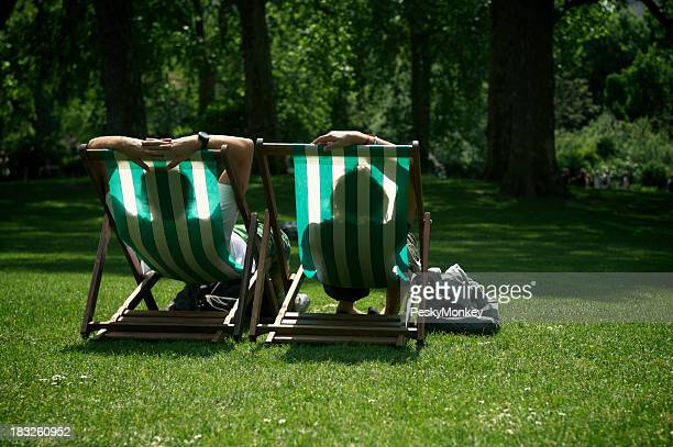 Two People Relaxing in Striped Deck Chairs London Park