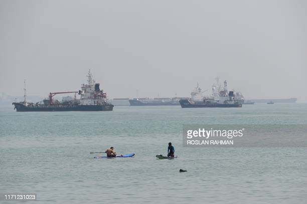Two people rest on their paddleboards in front of commercial vessels anchored at the Singapore Eastern anchorage in Singapore strait on September 26...