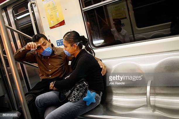 Two people ride the subway wearing surgical masks to help prevent being infected with the swine flu on May 3 2009 in Mexico City Mexico The Mexican...